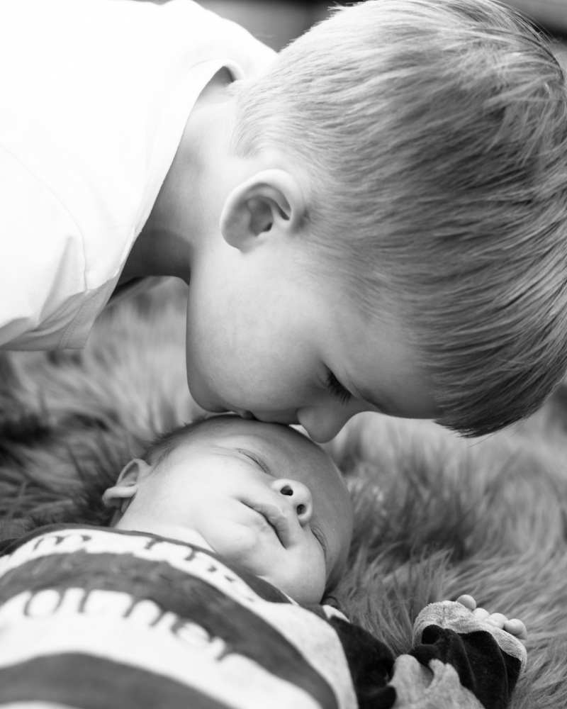Kisses for little brother, baby photographer Cumbria