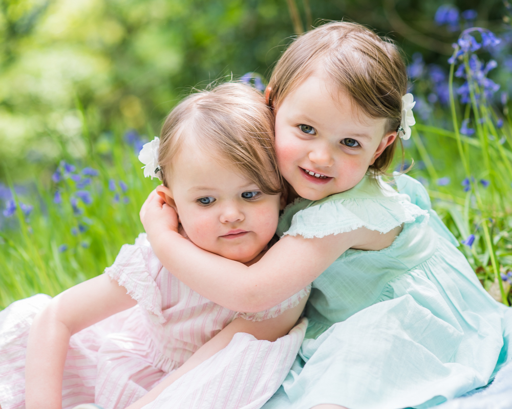Sisters cuddling, woodland bluebell photo session Sheffield
