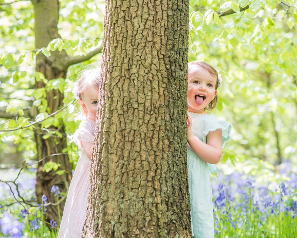 Twins hiding behind tree in Ecclesall woods