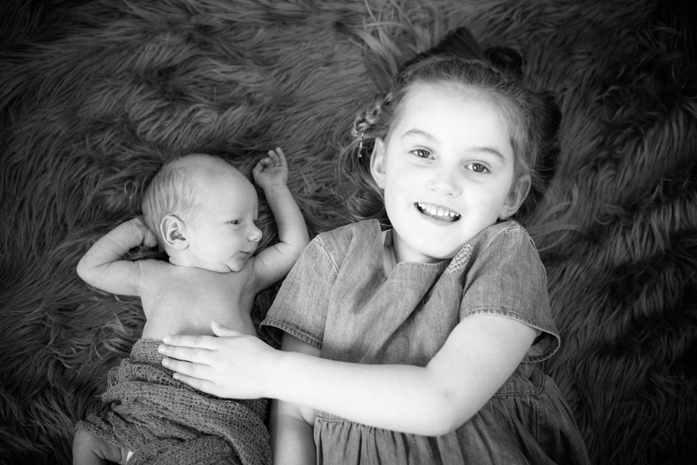 Cuddles with big sister, newborn photographer Cumbria