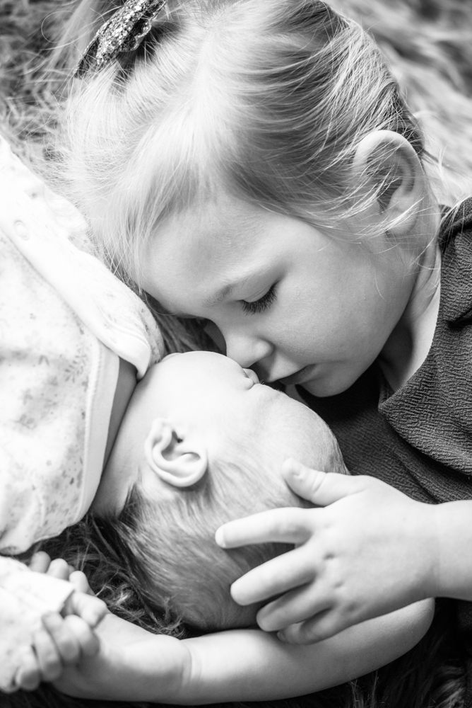 Kissing her little sister on newborn photo shoot