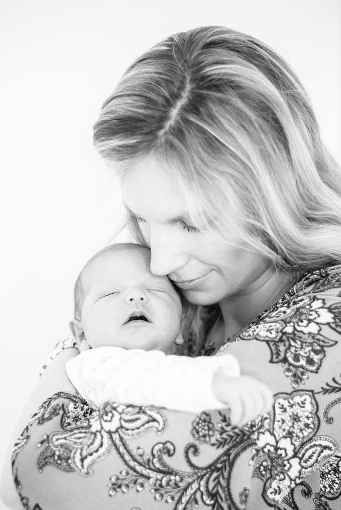 Mum snuggling baby Georgie on newborn photo session at home in Sheffield