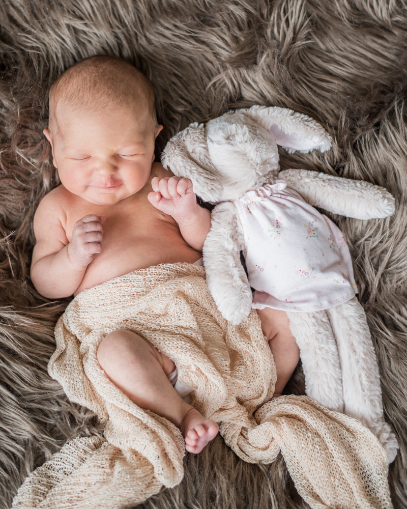 Smiling baby and rabbit toy, newborn photography in Carlisle