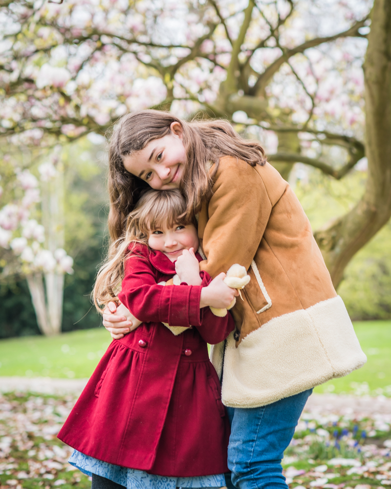 Sister cuddles in spring blossom, Carlisle baby photographers