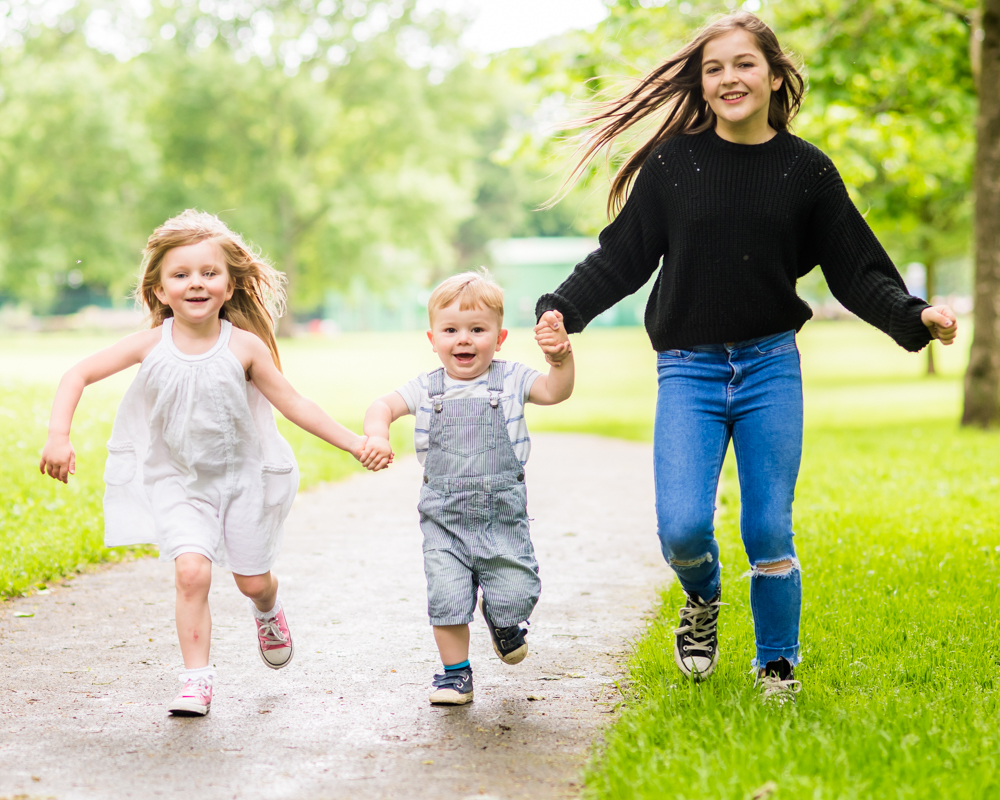 Siblings running, Carlisle family portraits in Bitts Park