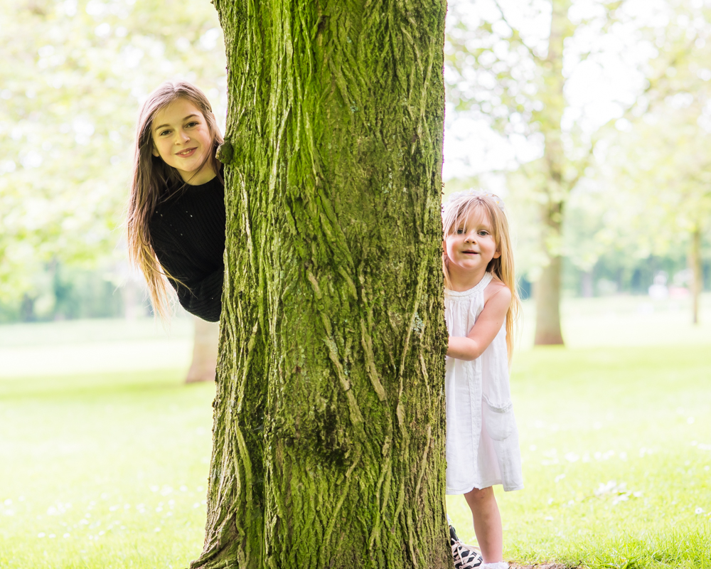 Katie and Abbie hiding, Carlisle family portraits in Bitts Park