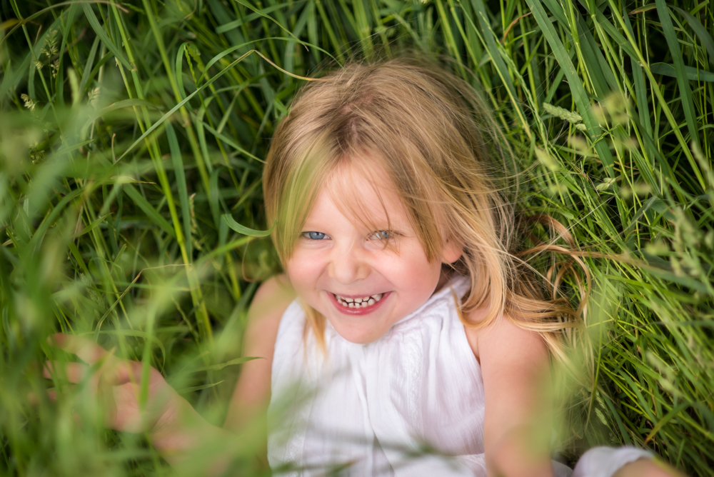 Katie hiding in long grass, Cumbria family photographers