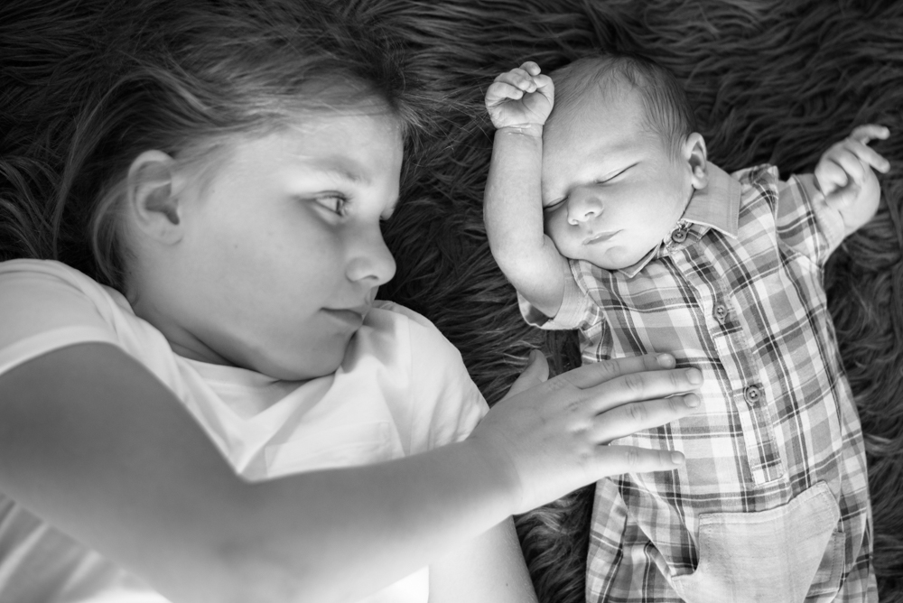 Cuddles from big sister, baby photographers Cumbria