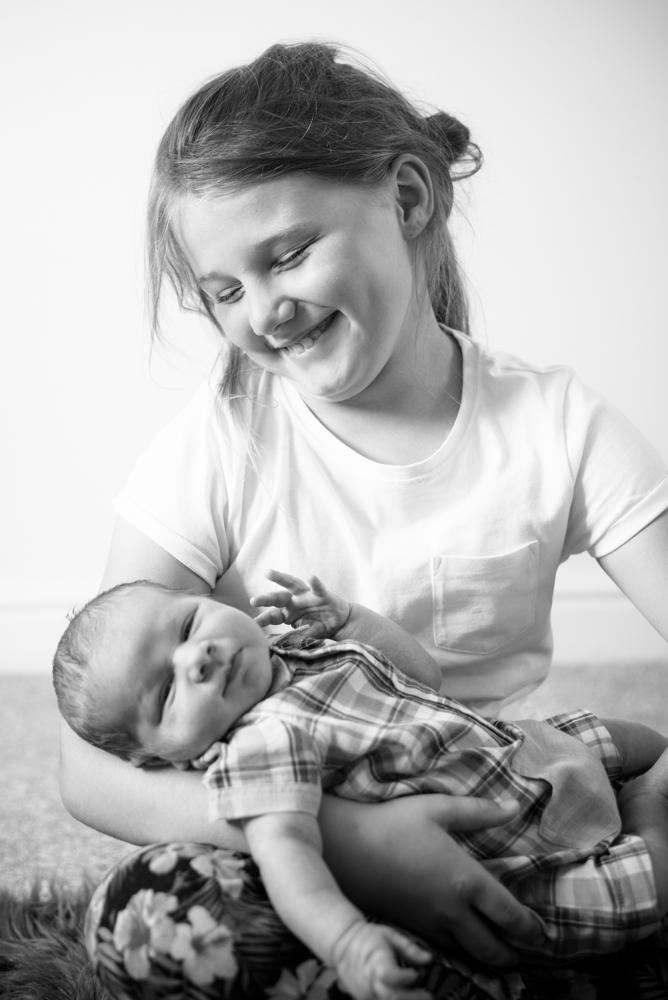 Big sister cuddling baby, newborn portraits Workington