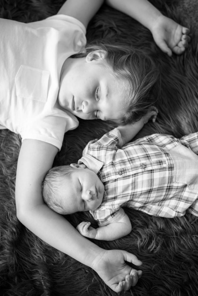 Siblings lying together, newborn photographer Keswick