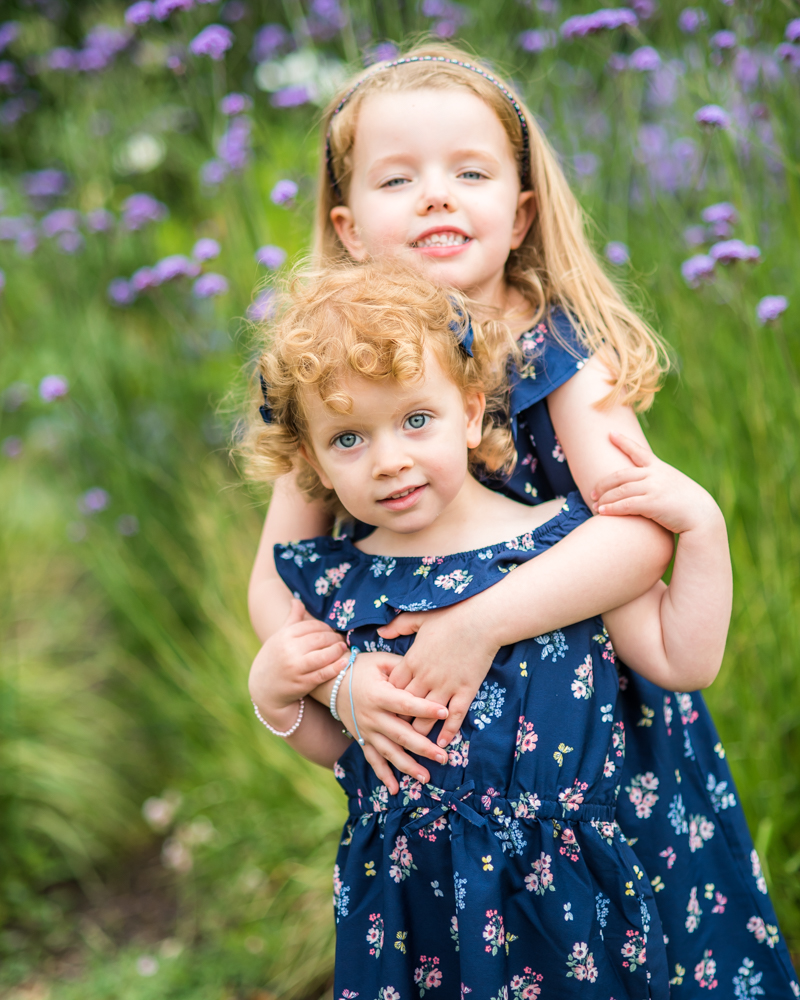 Sisterly cuddles in the flowers, baby portraits Sheffield