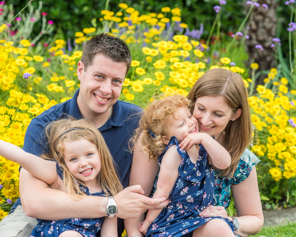 Family snuggles in yellow flowers, Cockermouth baby photographers
