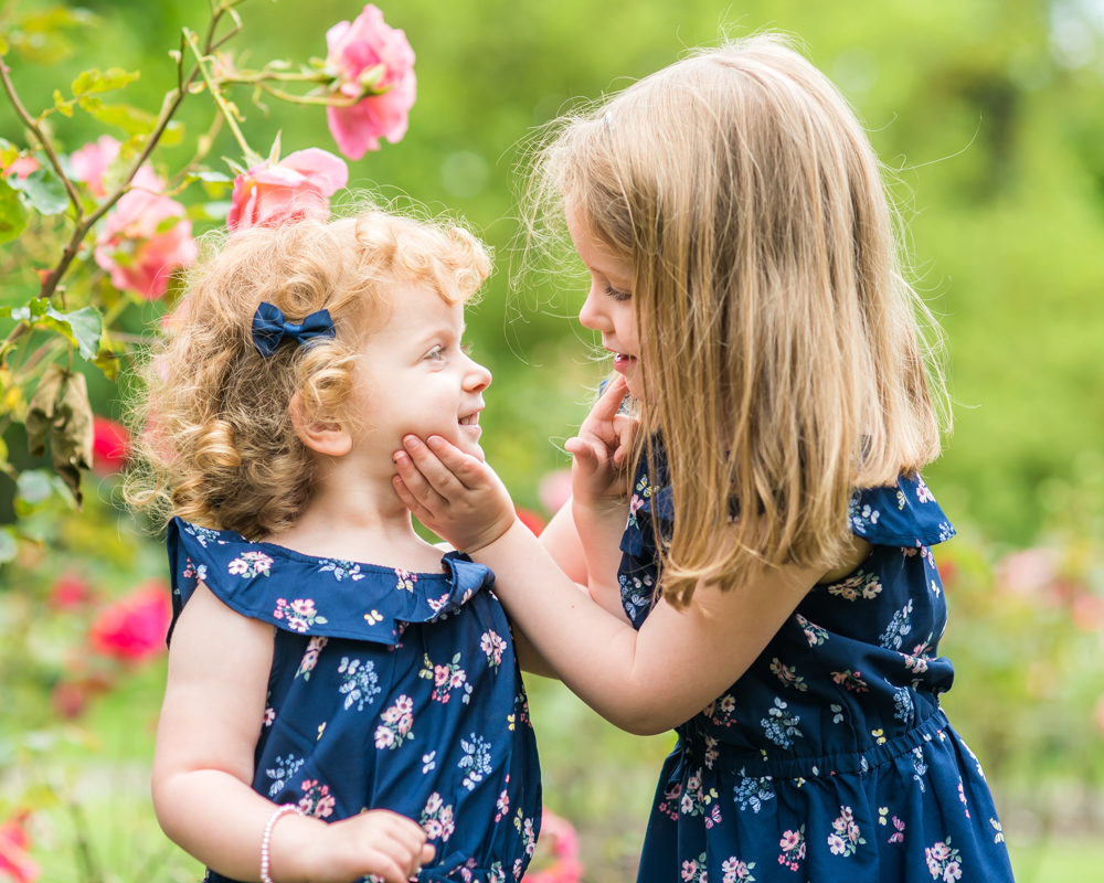 Sisters holding each other and smiling, Cumbria baby photographers
