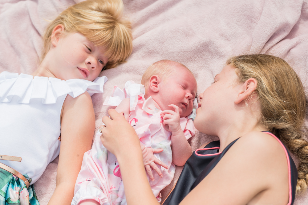 Cuddles with their sister, newborn photographer Carlisle