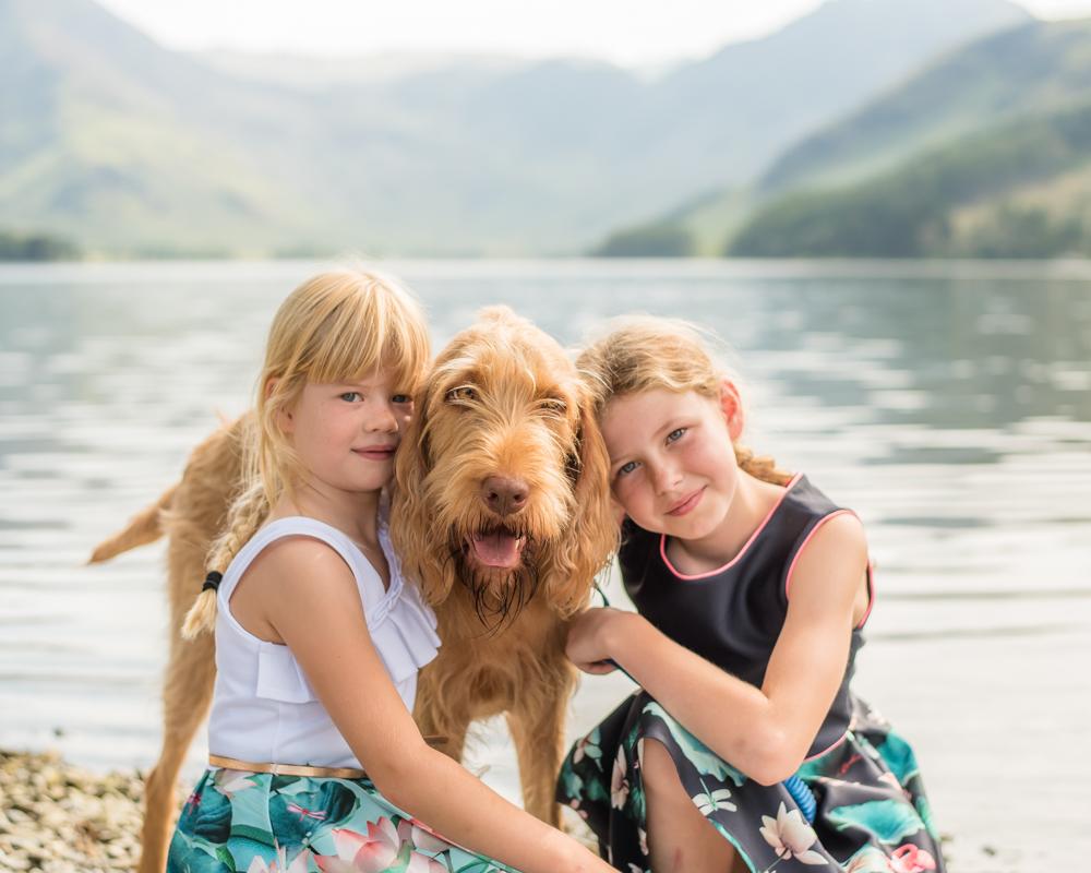 Girls cuddling Wally the dog, baby photographer Cockermouth
