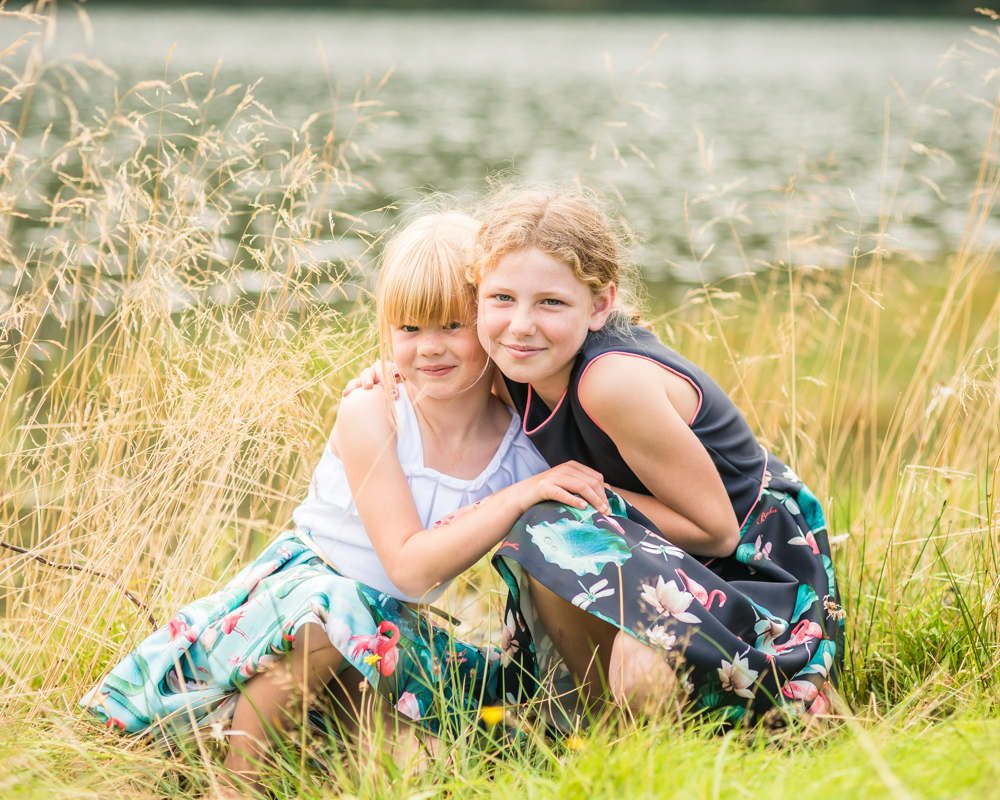 Sisters cuddling by Buttermere Lake, family photographer Keswick