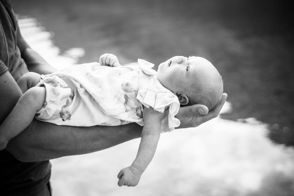 Tiny Beatrix in Dad's arms, newborn photographer Cumbria