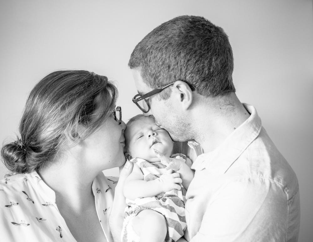 Mum and Dad kissing baby, natural newborn photographs