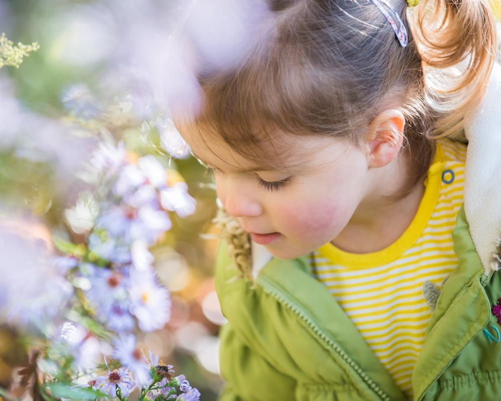 Jessie smelling flowers, baby portraits Dodd Wood